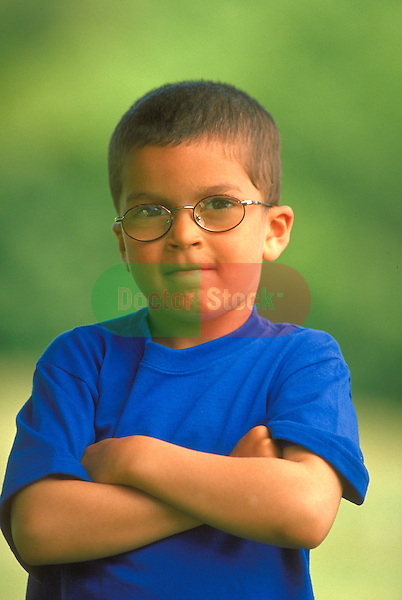 portrait of serious boy standing with arms crossed