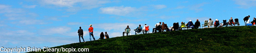 A group of peopel on a hillside under a pretty blue sky and clouds,  web banner photo, 1200x250 pixels. (Photo by Brian Cleary/www.bcpix.com) 1200x250 pixels and 500x100 pixels available.