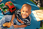 Education preschool 3-4 year olds portrait of boy looking up from toys smiling horizontal