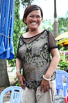 """Nguyen Thi Dung, 45, grins for a photograph near her drink stand in Da Nang, Vietnam. Dung's father was a soldier for the South Vietnamese army during the Vietnam War and died at 62 from complications related to Agent Orange exposure. She and an older brother were born with hip dysplasia that doctors say is linked to their father's exposure, and she suffers from neurological damage that causes one side of her mouth to droop and for her eyes and mouth to twitch uncontrollably. """"My son's condition is even worse,"""" she says. """"There are three generations in my family like this, and the doctors say that for all three generations, our condition is because of Agent Orange."""" The family survives partially on about $25 that each gets monthly from the Da Nang Association of Victims of Agent Orange/Dioxin, an aid group. The Vietnam Red Cross estimates that 3 million Vietnamese suffer from illnesses related to dioxin exposure, including at least 150,000 people born with severe birth defects since the end of the war. The U.S. government is paying  to clean up dioxin-contaminated soil at the Da Nang airport, which served as a major U.S. base during the conflict. But the U.S. government still denies that dioxin is to blame for widespread health problems in Vietnam and has never provided any money specifically to help the country's Agent Orange victims. May 30, 2012."""