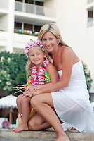 Mother and daughter with hula skirt and leis on vacation in Hawaii with hotel in rear