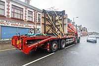 Pictured: The Banksy is transported on a flat bed lorry through Commercial Street. Wednesday 29 May 2019<br /> Re: Contractors are working to move Banksy's Season Greeting, now owned by John Brandler, which appeared on a garage wall in Port Talbot, to a new location in the same town in south Wales, UK.