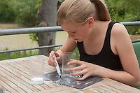 Mädchen, Kind bastelt eine Becherlupe, Beobachtungsgefäß aus 2 durchsichtigen Plastikbecher, einem Stück Styropor und Frischhaltefolie. 5. Schritt: Bechergroßer Kreis wird auf der Frischhaltefolie  aufgemalt