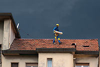 Milano, periferia nord. Lavori di manutenzione sul tetto di un palazzo residenziale sotto un cielo plumbeo --- Milan, north periphery. Maintenance work on the roof of a residential building under a leaden sky