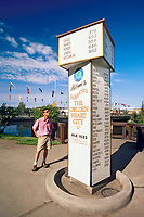Man views the mile chart on the End of Alaska highway sign at the golden heart plaza in downtown Fairbanks, Alaska.