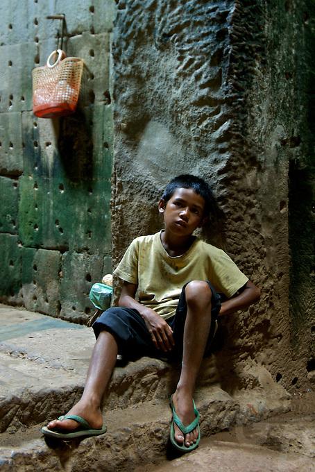 CAMBODIA 2007,SIAM REAP Boy resting inside the Preak Khan temple, near Angkor Wat