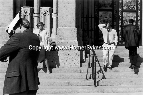 Group of men and women shading them selves from the hot sun. Cathedral steps. San Francisco California USA, 2001 .