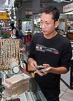Myanmar, Burma, Yangon.  A Money-changer Changing Burmese Kyat for U.S. Dollars.