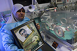The mother of Palestinian prisoner Fahmi Abu Salah, holds her son picture as she stands next to his baby boy who was conceived with Abu Salah's sperm smuggled out of an Israeli prison, at a hospital in Gaza City January 23, 2014.  May, the Gaza wife of a Palestinian prisoner in an Israeli jail, gave birth to her baby boy on Thursday in the second successful smuggling of sperm to lead to a pregnancy in the embattled coastal enclave. Photo by Mohammed Asad