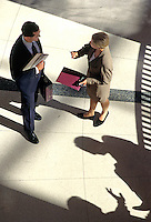 Businessman and businesswoman talking in lobby of office building. Business people. United States.