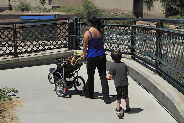Mother pushing baby stroller, with son on scooter, Denver, Colorado. .  John offers private photo tours in Denver, Boulder and throughout Colorado. Year-round Colorado photo tours.