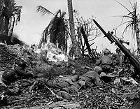 Men of the 7th Div. using flame throwers to smoke out Japs from a block house on Kwajalein Island, while others wait with rifles ready in case Japs come out. February 4, 1944.  Cordray. (Army)<br /> NARA FILE #:  iii-SC-212770<br /> WAR & CONFLICT BOOK #:  1187