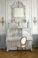 The hand-painted gilded piano in the living room matches the boiserie and wall lights