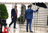 An aide holds an umbrella for United States President Donald J. Trump as he departs the White House, Saturday, June 20, 2020, in Washington, DC. Trump is attending a Make America Great Again campaign rally in Tulsa, Oklahoma, the first since the outbreak of the coronavirus pandemic postponed much of his 2020 reelection campaign last spring.  <br /> Credit: Mike Theiler / Pool via CNP/AdMedia