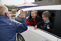 """Samaritans Feet Executive Director Kyle Alexander (from left) high-fives Jerry Eley, 8 and Jaxon Eley, 6, of Springdale, Saturday, April 3, 2021 at Sam's Furniture in Springdale. Samaritan's Feet distributed approximately 720 pairs of shoes to pre-registered students from 18 elementary schools across Springdale in a """"drive-thru"""" event. Each recipient received a """"Hope Tote"""" drawstring book bag that contains a new pair of athletic shoes, socks, hygiene kit and a """"hope note"""" with an encouraging message submitted online from Samaritan's Feet supporters. Check out nwaonline.com/210404Daily/ for today's photo gallery. <br /> (NWA Democrat-Gazette/Charlie Kaijo)"""