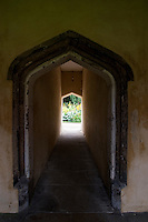 An arched door leads under the medieval buildings surrounding the Cloister or Great Quad at Magdalen College, Oxford