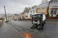 """Pictured: A Council brush cleans up in Waun-Wen Road in the Mayhill area of Swansea, Wales, UK. Friday 21 May 2021<br /> Re: Gangs of """"yobs"""" have been setting fire to cars and rolling them down a hill in Swansea, Wales, UK.<br /> South Wales Police said they attended """"large scale disorder"""" in the Mayhill area of the city on Thursday evening."""