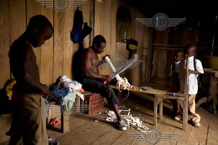 A man carves a drum stick while his children look on in San Miguel, an Afro Ecuadorian community located three hours up the Cayapas River in the province of Esmeraldas.