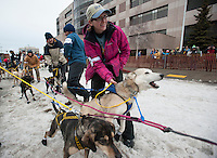 Volunteer dog handler Aleria Knudson helps hold back a team at the ceremonial start of the 43rd Iditarod dog sled race in downtown Anchorage. 79 mushers made their way 11 miles through the slushy streets of Anchorage in unseasonably warm weather and early rain. This year's official re-start will begin in Fairbanks because of poor trail conditions in Southcentral Alaska.