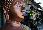 Bronze Sukhothai style Buddha statue with King Chulalogkorn in background.