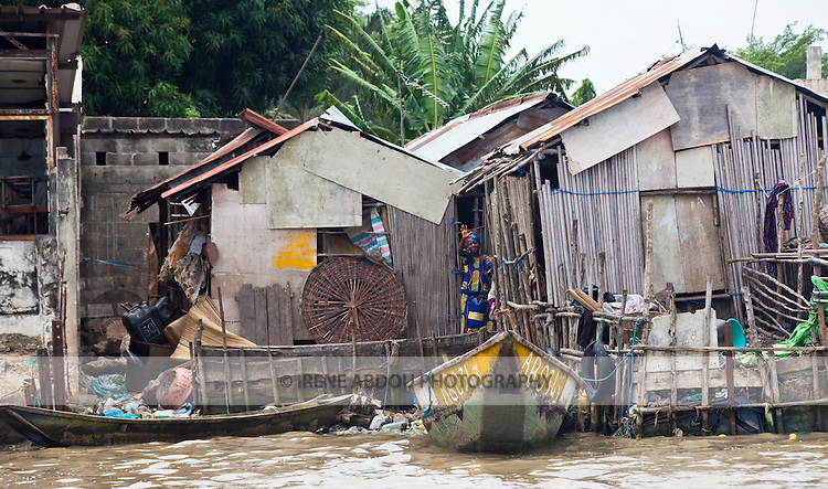 Ramshackle houses line the coast of Benin near Cotonou.  Living next to the ocean, boats become a common means of transportation.