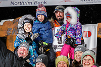 Pete Kaiser and family pose with friends and family from Bethel, Alaska at the Nome finish line after Pete wins the 2019 Iditarod Trail Sled Dog Race. Pete's winning time is 9 days 12 hours 39 minutes and 6 seconds<br /> <br /> Photo by Jeff Schultz/  (C) 2019  ALL RIGHTS RESERVED