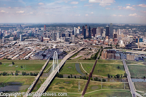 aerial photograph of the Dallas, Texas skyline, the Trinity River in the foreground, the Margaret Hunt Hill Bridge at center left