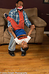3 year old boy at home roughhousing playing with father flipping in his arms