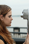 girl posing looking into binoculars on the harbor