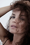 Close-up beauty portrait of a young woman with sensual unguarded look and long curly brown hair falling on her beautiful face Image © MaximImages, License at https://www.maximimages.com
