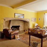 The study has been painted a cheerful buttercup yellow which also serves to highlight the colour of the mellow old stones of the massive inglenook fireplace