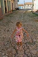 Little blond girl playing on a cobblestone street nearby Plaza Mayor, Trinidad, Cuba.