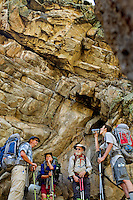 Photo story of Philmont Scout Ranch in Cimarron, New Mexico, taken during a Boy Scout Troop backpack trip in the summer of 2013. Photo is part of a comprehensive picture package which shows in-depth photography of a BSA Ventures crew on a trek.  In this photo a BSA Venture Crew takes a break from climbing in the shade of the underside of a rocky cliff in the backcountry at Philmont Scout Ranch.   <br /> <br /> The  Photo by travel photograph: PatrickschneiderPhoto.com