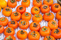 Yangshuo, China.  Persimmons for Sale at Sidewalk Fruit Stand.