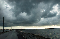 The single road that leads from the predominantly Native American community of Isle Jean Charles, Louisiana viewed toward the mainland, as a storm looms above. The road often floods and is in need of constant repair due to erosion. The island is clinging to life after decades of severe erosion of coastal marshes that once provided a buffer against hurricanes and high tides. Only 70 or so residents remain, down from 300 at its peak.