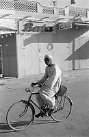 A man riding a bicycle clad in white with a headdress. A Bata shoe advert in the backdrop - Khartoum, Sudan - November-1961