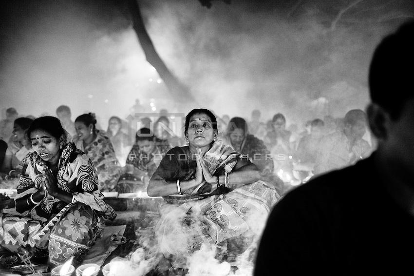 A Hindu woman prays while thick clouds of incense raise around her during the  Kartik Brati or Rakher Upobash religious festival in Barodi,  Near Dhaka, Bangladesh