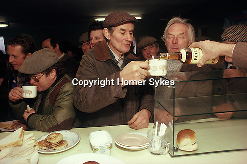 Knighton, Shropshire. 1985.  <br /> Farmers enjoy a cup of tea with a splash of Bell's whisky at the annual Farmers Christmas Market and auction.