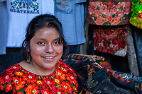 Chichicastenango, Guatemala.  Young Quiche Woman, Vendor of Clothing and Fabric Items.