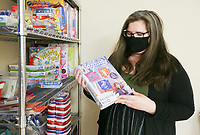 """Abra Morgan, advocate supervisor and license social worker, over a shelf of toys and supplies, Thursday, November 19, 2020 at CASA of Northwest Arkansas in Springdale. Court appointed special advocates can use the donation room to find items that children need or games and activities that can help the advocate connect with the child. CASA is seeking out volunteer court appointed special advocates, volunteers who are specially trained to support and speak up for the needs of children in the foster care system. """"We have a steady number of foster kids coming into care so we're always trying to recruit new volunteers to keep up with that rising number,"""" said Abra Morgan, advocate supervisor and license social worker, who manages about 30 to 35 volunteer advocates. """"Our goal is to have volunteers waiting for kids. When we have a new kid, we can match that kid with the perfect volunteer instead of having 20 kids and two volunteers."""" CASA hosts a virtual orientation for new volunteers every third Thursday of the month. Check out nwaonline.com/201120Daily/ for today's photo gallery. <br /> (NWA Democrat-Gazette/Charlie Kaijo)"""