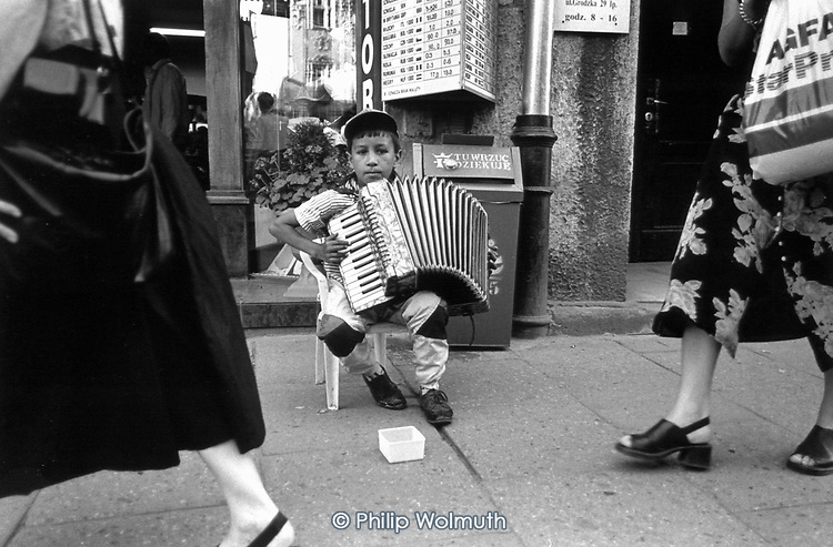 A Roma boy plays the accordion for small change on a Krakow street.