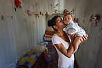 """THIS PHOTO IS AVAILABLE AS A PRINT OR FOR PERSONAL USE. CLICK ON """"ADD TO CART"""" TO SEE PRICING OPTIONS.   A Roma woman holds her baby inside a shipping container that has been converted into a house in Makis, a village outside of Belgrade, Serbia. These Roma families were evicted from an urban squatter settlement in 2012 to make way for construction of new apartments and office buildings. The shipping containers they now call home, which were provided at no cost by local authorities, are far from the city center."""
