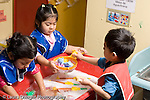 Educaton preschool  3-4 year olds two girls and a boy playing at water table horizontal boy and girl interacting