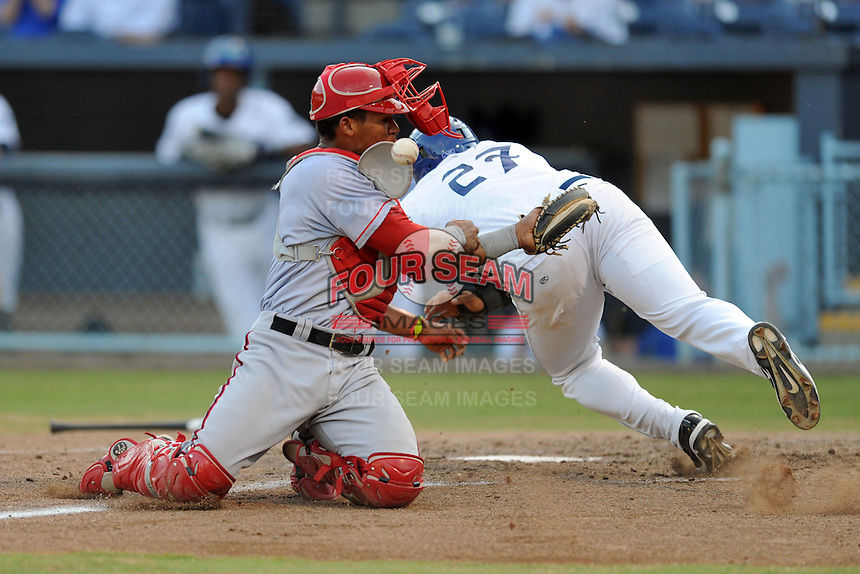 Hagerstown Suns catcher Pedro Severino #4 has the ball knocked loss by a hard charging Dillon Thomas #27 during a play at the plate during a game against the Asheville Tourists at McCormick Field on May 28, 2013 in Asheville, North Carolina. The Tourists won the game 9-4. (Tony Farlow/Four Seam Images)