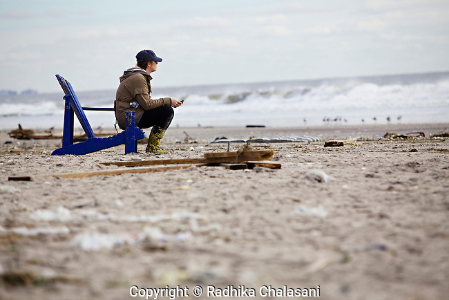 BELLE HARBOR, NEW YORK-NOVEMBER 01: A young woman sits on the beach in this Rockaway, Queens neighborhood after Hurricane Sandy November 1, 2012. A large number of homes and businesses were destroyed by the storm and much of the area is without power and many head to the beach in hopes of finding a cell phone signal.