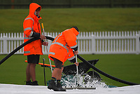 Staff clear water from the covers before the cancellation of the Ford Trophy one-day cricket match between the Central Stags and Wellington Firebirds at Fitzherbert Park in Palmerston North, New Zealand on Tuesday, 8 December 2020. Photo: Dave Lintott / lintottphoto.co.nz