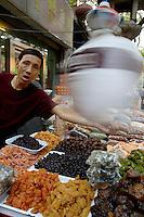 Man selling dried fruit at the market, Daqingzhen Si, Muslim District, Xian, Shaanxi, China.