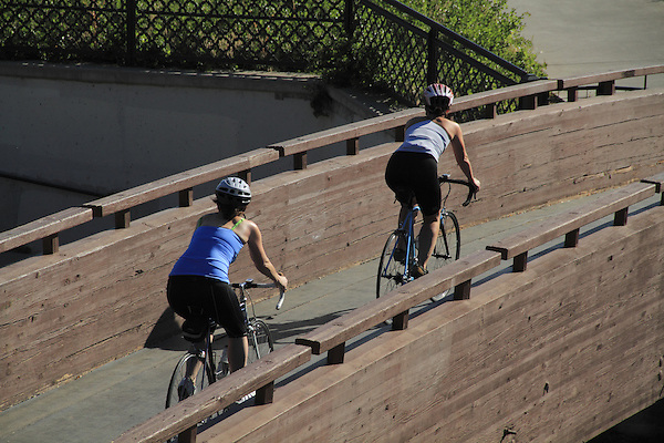 Two women riding their bikes on a bike path in Denver, Colorado. .  John offers private photo tours in Denver, Boulder and throughout Colorado. Year-round.