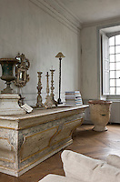 A marbleised wooden altar serves as a sideboard against one wall of the salon on which is displayed a collection of church candlesticks