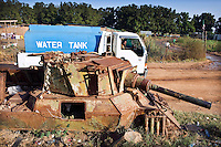 A tanker carrying drinking water passes an old military tank, left behind during the civil war between the North and the South.